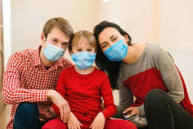 Młoda rodzina w ochronne maski medyczne. zapobieganie koronawirusowi. zostań w domu. kwarantanna domowa.