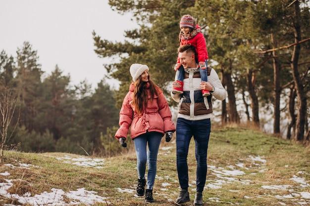Młoda rodzina wpólnie chodzi w lesie przy zima czasem