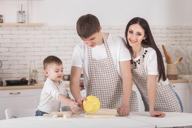 Młoda rodzina wspólne gotowanie. mąż, żona i ich małe dziecko w kuchni. rodzina wyrabia ciasto z mąką. ludzie gotują obiad lub śniadanie.