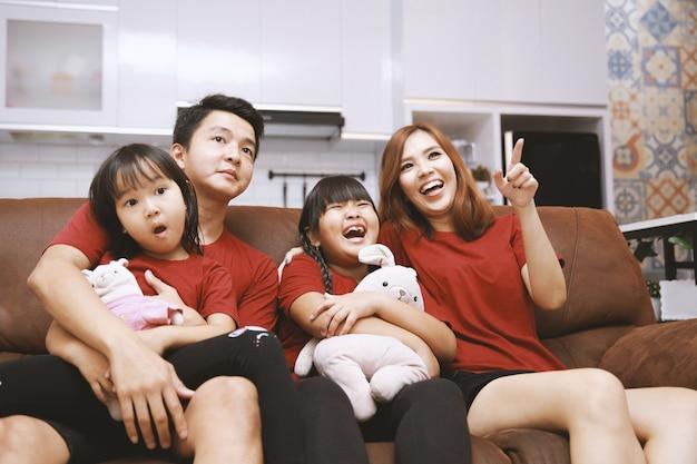 Młoda rodzina wspólnie oglądająca telewizję w domu i bawiąca się razem