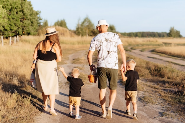 Młoda rodzina z dwójką dzieci latem spaceruje na łonie natury poza miastem