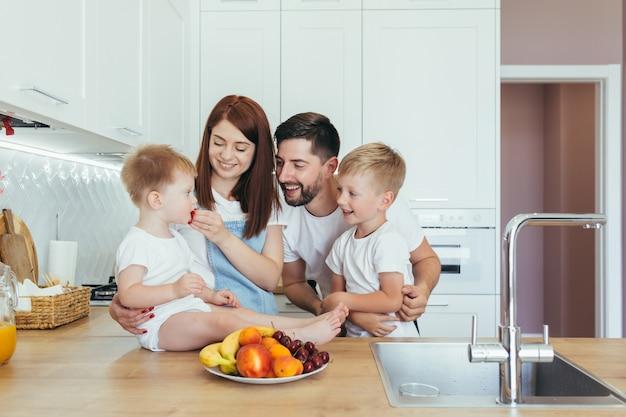 Młoda rodzina z dwójką małych dzieci jedzących śniadanie w pięknej białej kuchni