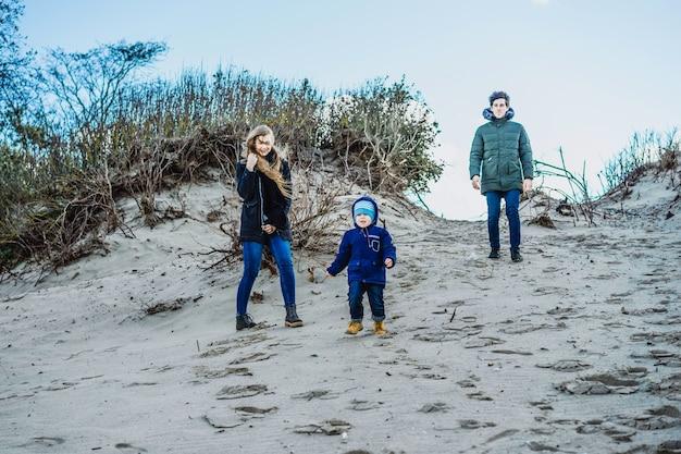 Młoda rodzina z dziećmi spędza weekend na brzegach zimnego morza bałtyckiego