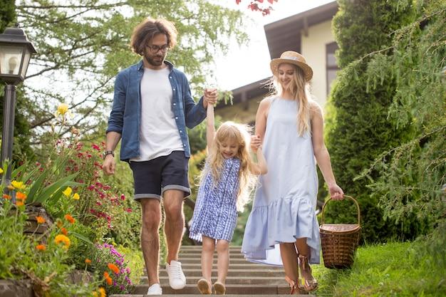 Młoda rodzina z koszem po pikniku idąc po schodach poza w parku