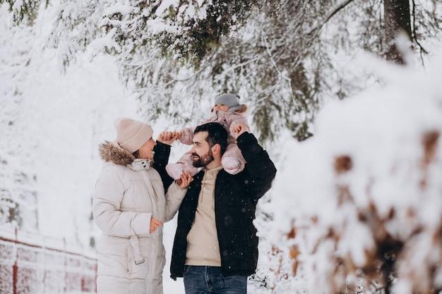 Młoda rodzina z małą córeczką w lesie zimą pełną śniegu