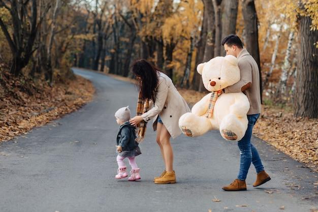 Młoda rodzina z małą córką przy jesień parka drogi teraźniejszości niedźwiedzia dużą zabawką