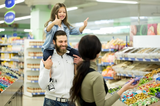Młoda rodzina z małą dziewczynką wybiera cukierki i czekoladę w dużym sklepie, supermarkecie.