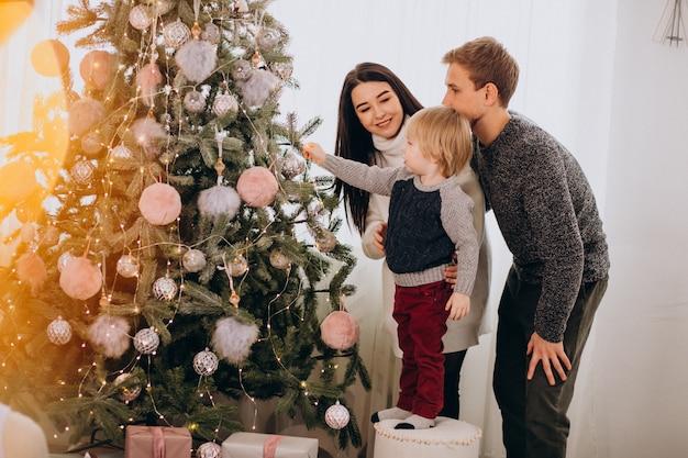 Młoda rodzina z małym synem dekoruje choinki