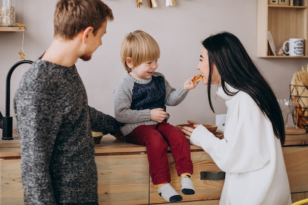 Młoda rodzina z małym synem przy kuchnią na bożych narodzeniach