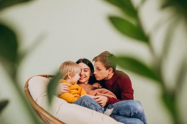Młoda rodzina z małym synem siedzi w krześle