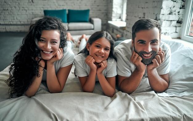 Młoda rodzina z małymi dziećmi do łóżka w sypialni