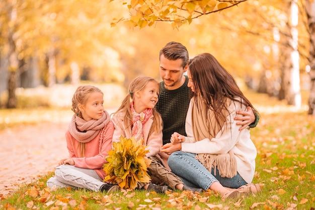 Młoda rodzina z małymi dziećmi w jesień parku w słoneczny dzień. portret rodzinny jesień