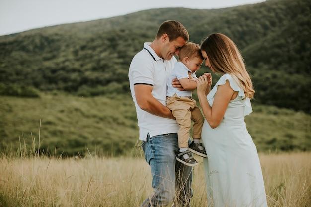 Młoda rodzina z uroczym małym chłopcem bawi się na świeżym powietrzu w letnim polu