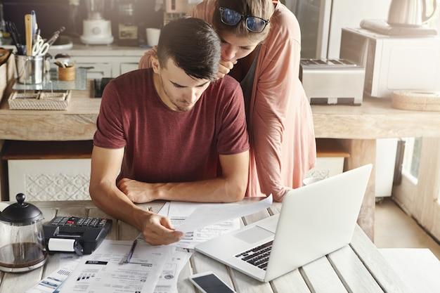 Młoda rodzina zarządza budżetem, przegląda swoje konta bankowe za pomocą zwykłego laptopa i kalkulatora w kuchni. mąż i żona robią razem papierkową robotę, płacąc podatki online na komputerze przenośnym