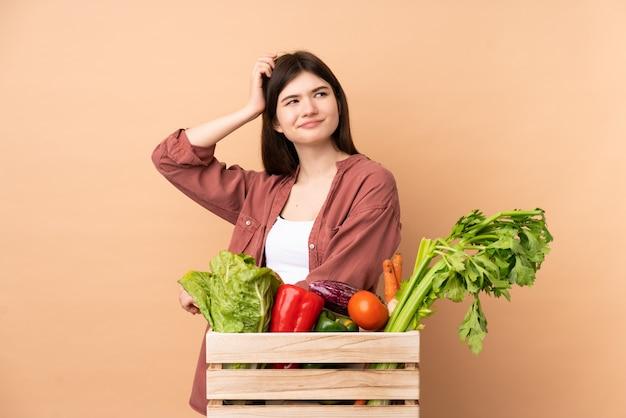 Młoda rolnik dziewczyna ze świeżo zebranych warzyw w polu, mając wątpliwości podczas drapania głowy