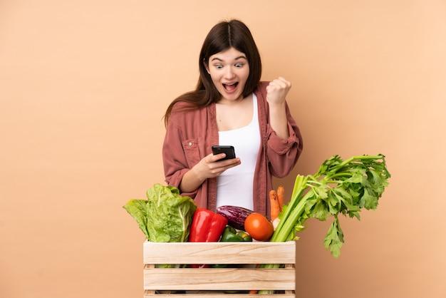 Młoda rolnik dziewczyna ze świeżo zebranych warzyw w pudełku zaskoczony i wysyłając wiadomość