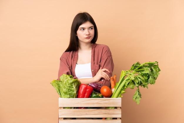 Młoda rolnik kobieta ze świeżo zebranych warzyw w pudełku z mylącym wyrazem twarzy