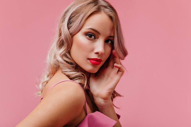 Młoda romantyczna ładna blondynka o wyglądzie modela z jasnym makijażem pozuje do portretu na różowej ścianie na białym tle