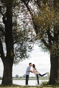 Młoda romantyczna para dobrze się bawi w słoneczny letni dzień w pobliżu jeziora. wspólne spędzanie czasu na wakacjach. mężczyzna i kobieta obejmują się i całują.