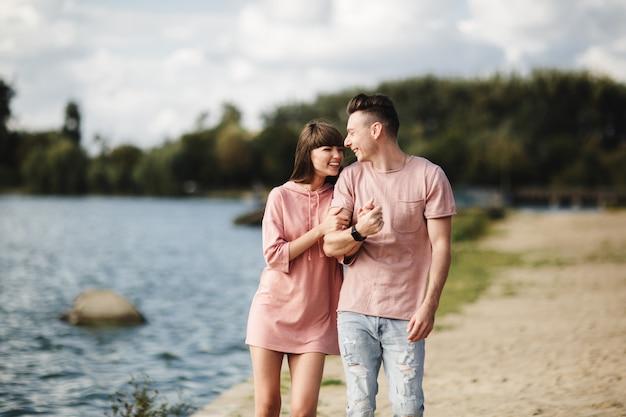 Młoda romantyczna para dobrze się bawi w słoneczny letni dzień w pobliżu jeziora. wspólne spędzanie czasu na wakacjach. mężczyzna i kobieta się przytulają