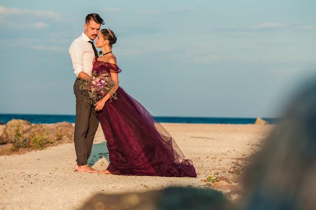 Młoda romantyczna para relaksuje na plaży ogląda zmierzch
