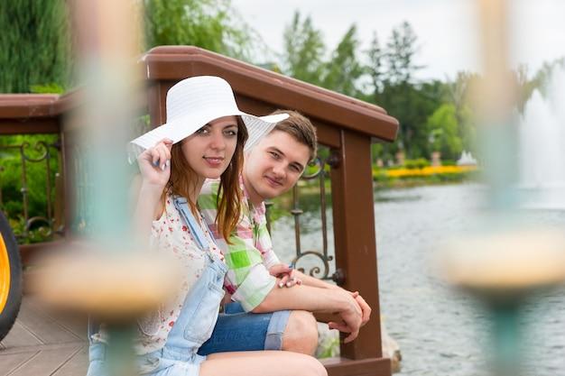 Młoda romantyczna para siedzi na drewnianym tarasie naprzeciwko sztucznego jeziora w parku z fontanną i różnymi drzewami w tle