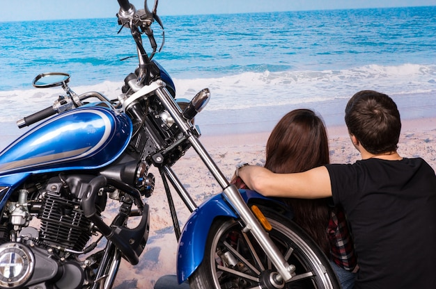 Młoda romantyczna para siedzi z ramionami wokół siebie na piaszczystej plaży z motocyklem