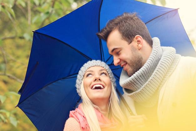 Młoda romantyczna para z parasolem w parku jesienią