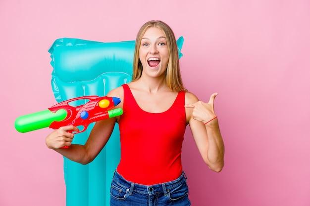 Młoda rosjanka bawiąca się pistoletem na wodę z nadmuchiwanym materacem zaskoczona, wskazując palcem, uśmiechając się szeroko