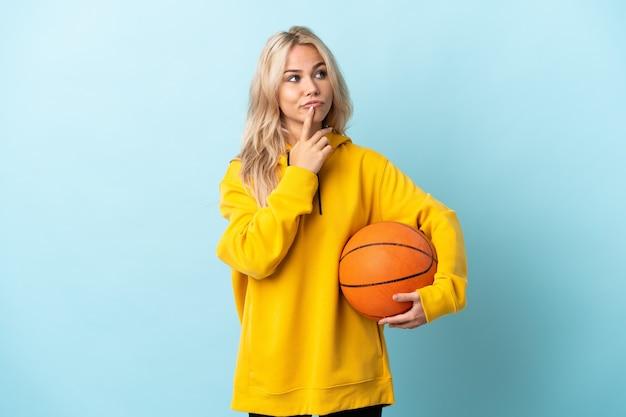 Młoda rosjanka gra w koszykówkę na białym tle na niebieskiej ścianie, mając wątpliwości, patrząc w górę