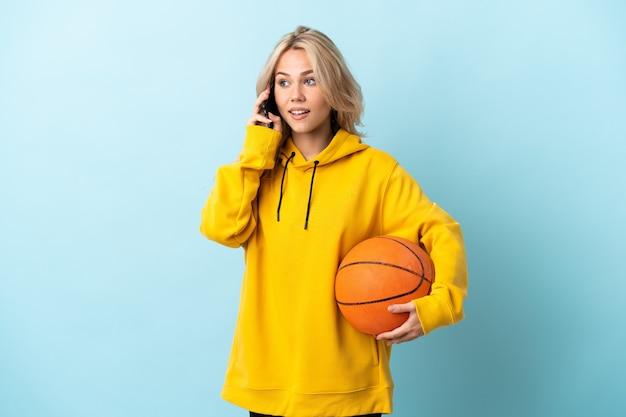 Młoda rosjanka gra w koszykówkę na białym tle na niebieskiej ścianie, prowadząc rozmowę z telefonem komórkowym