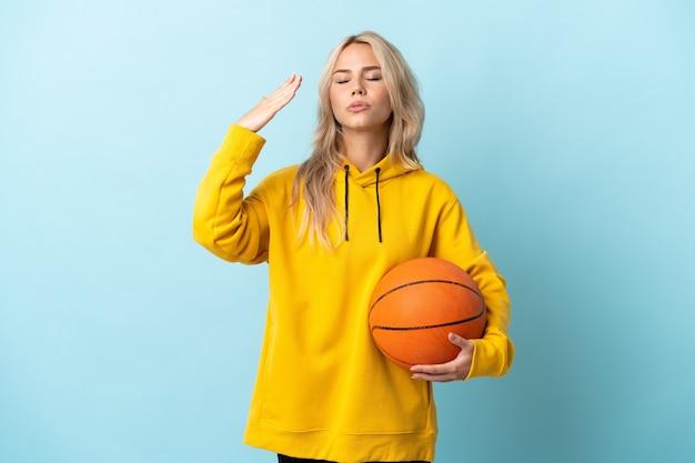 Młoda rosjanka gra w koszykówkę na białym tle na niebieskiej ścianie z wyrazem zmęczony i chory
