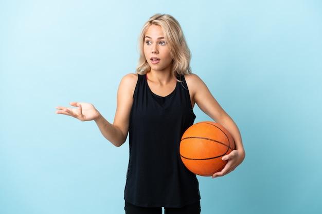 Młoda rosjanka gra w koszykówkę na białym tle na niebiesko z wyrazem zaskoczenia, patrząc z boku