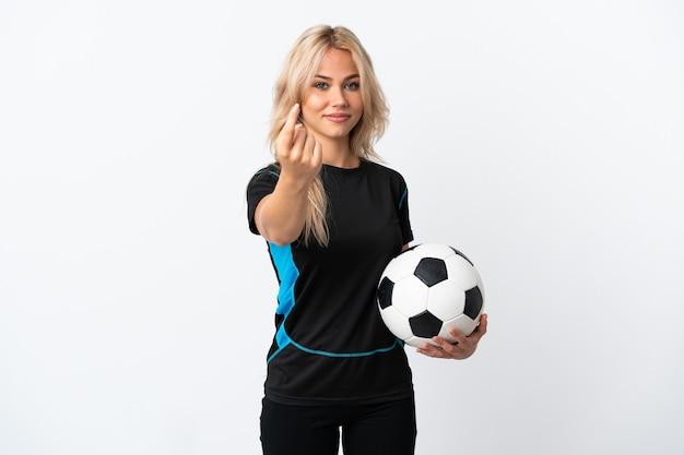 Młoda rosjanka gra w piłkę nożną na białym tle na białej ścianie robi nadchodzący gest