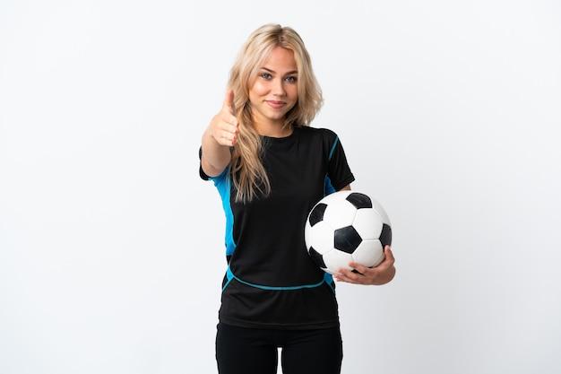 Młoda rosjanka gra w piłkę nożną na białym tle na białej ścianie, ściskając ręce za zamknięcie dobrą ofertę