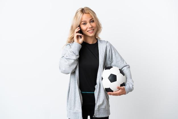 Młoda rosjanka, grając w piłkę nożną na białym tle na białej ścianie, prowadząc rozmowę z kimś przez telefon komórkowy