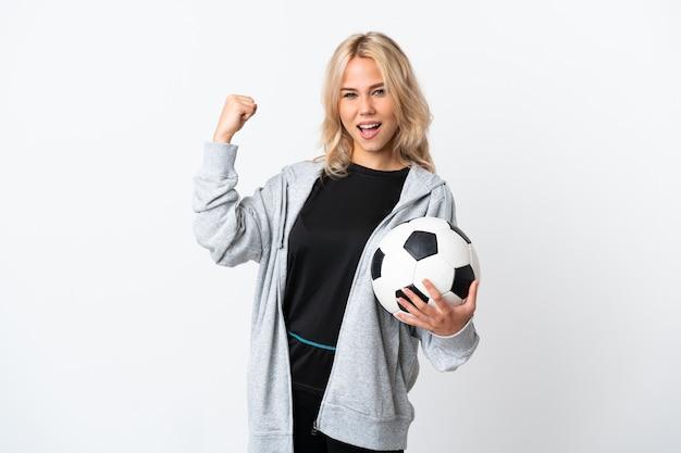 Młoda rosjanka, grając w piłkę nożną na białym tle na białej ścianie świętuje zwycięstwo