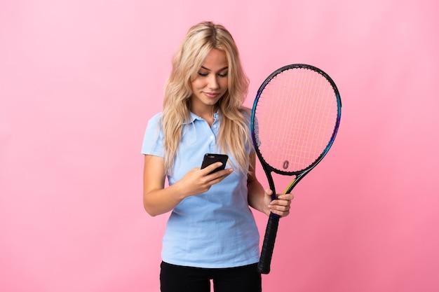 Młoda rosjanka, grając w tenisa na białym tle na fioletowym tle, wysyłając wiadomość z telefonu komórkowego