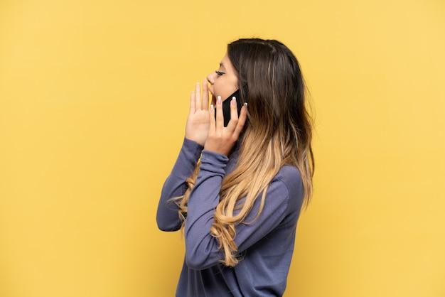 Młoda rosjanka korzystająca z telefonu komórkowego na żółtym tle krzyczy z szeroko otwartymi ustami