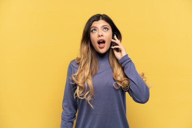 Młoda rosjanka korzystająca z telefonu komórkowego na żółtym tle patrząc w górę i ze zdziwionym wyrazem twarzy