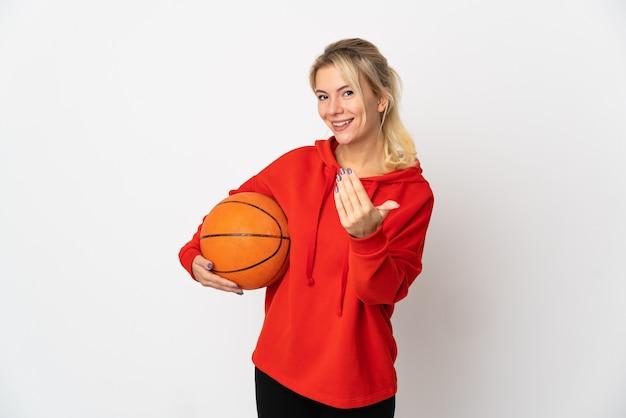Młoda rosjanka na białym tle na białej ścianie, gra w koszykówkę i robi nadchodzący gest