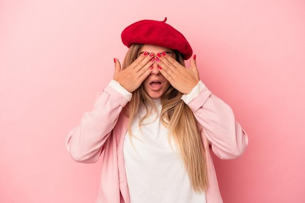 Młoda rosjanka na białym tle na różowym tle ma ból głowy, dotykając przodu twarzy.