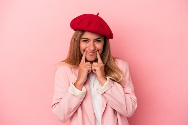 Młoda rosjanka na białym tle na różowym tle obejmujące uszy rękami.