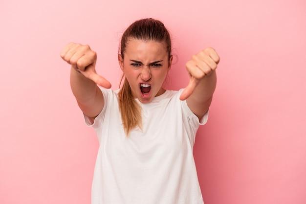 Młoda rosjanka na białym tle na różowym tle pokazując kciuk w dół i wyrażając niechęć.