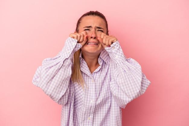 Młoda rosjanka na białym tle na różowym tle pokazując pięść do kamery, agresywny wyraz twarzy.