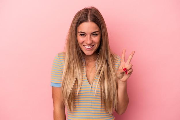 Młoda rosjanka na białym tle na różowym tle uśmiecha się, wskazując palcami na usta.