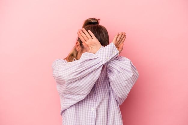 Młoda rosjanka na białym tle na różowym tle zakrywająca uszy rękami starając się nie słyszeć zbyt głośnego dźwięku.