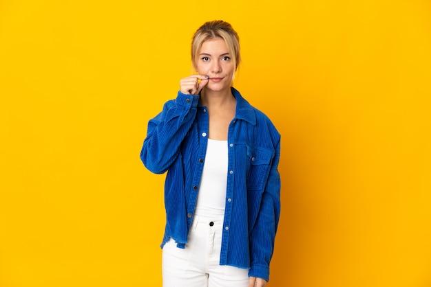 Młoda rosjanka na białym tle na żółtej ścianie przedstawiający znak gestu ciszy