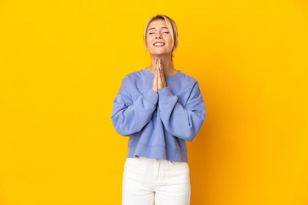 Młoda rosjanka na białym tle na żółtym tle trzyma dłoń razem. osoba o coś prosi