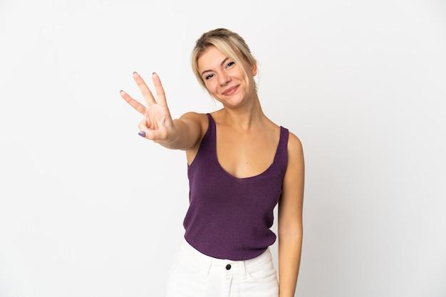 Młoda rosjanka na białym tle szczęśliwa i licząc trzy palcami